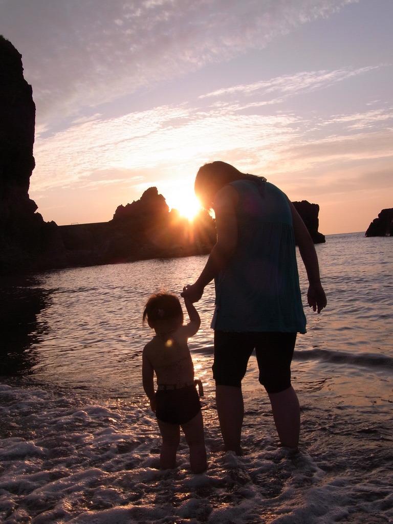 夕日沈む海辺にママと娘