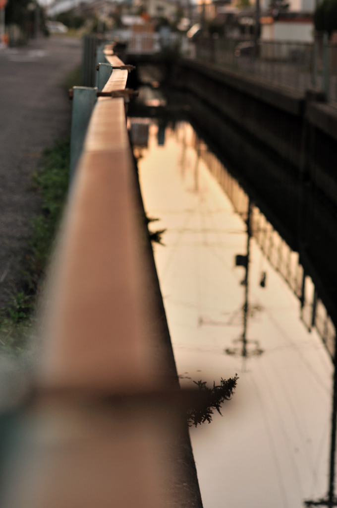 住宅街の水路フェンスに夕方の色