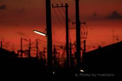 夕暮れの空 連なる電柱に一灯の明かり