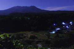 月明かりに照らされる御嶽山と農村