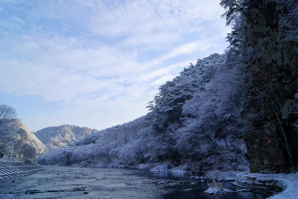 雪の久慈川のへつりと朝日を受ける大だるま岩
