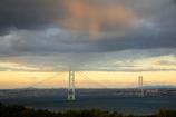 明石大橋の上空よりオレンジの光が降り注ぐ