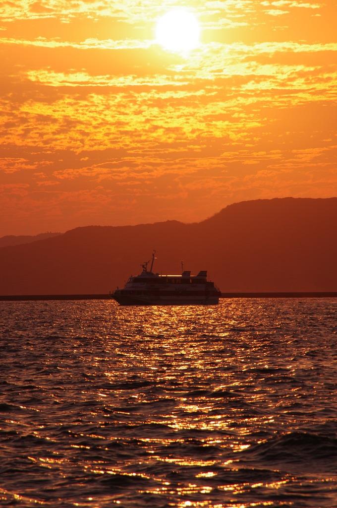 夕日色の海を航行