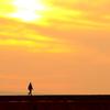 夕日を背にして歩く男