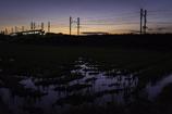「刈り入れ後の田圃と薄暮の列車」