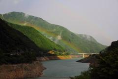 ダム湖上にかかる虹