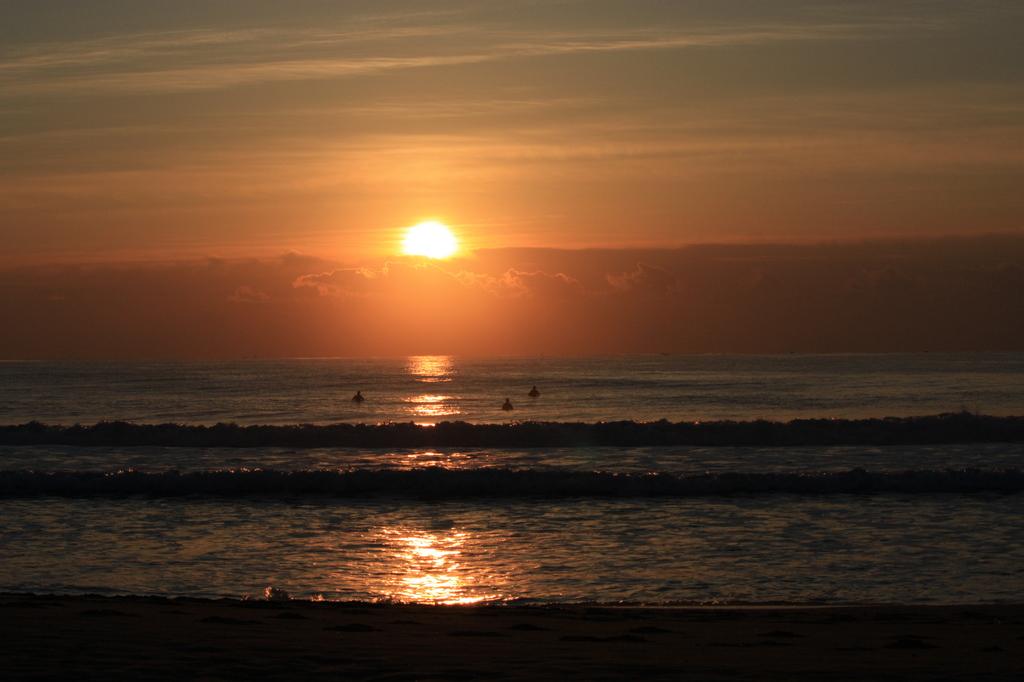 朝日とサーファー