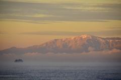 朝日に染まる雪山と多景島