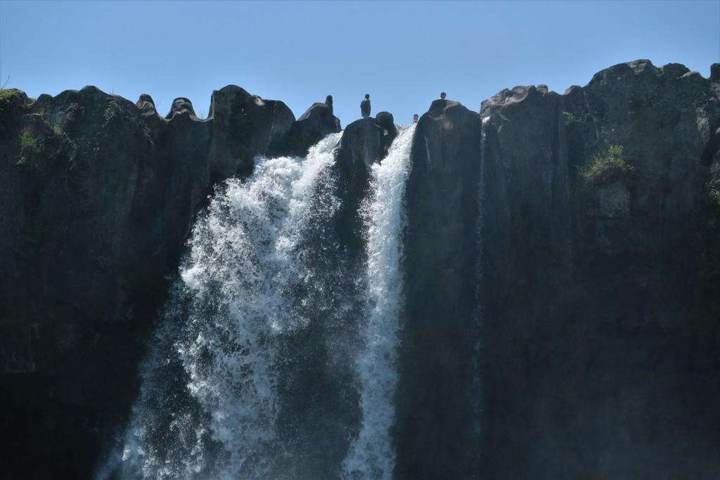 滝の上から眺める人