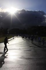 太陽の下を走る人々