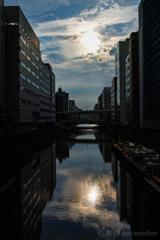 ビル間の川に朝日