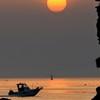 女岩越しの朝日とアオサギとボート