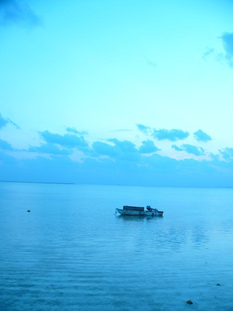 沖縄竹富島にて ポツンと浮かぶ小舟と夕空