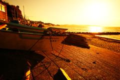 朝陽を浴びる海と漁船