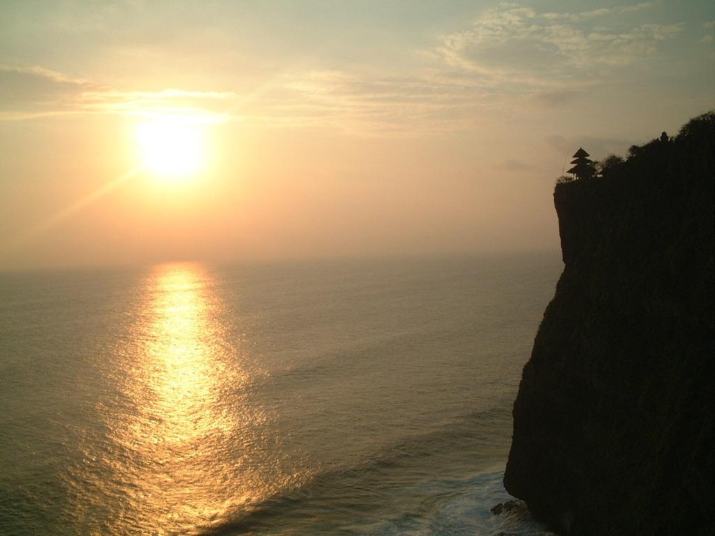 崖の寺院と夕日と海