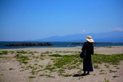 潮風に吹かれて古に思いを馳せる旅人一人
