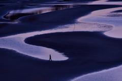 夕日が沈んだ後の干潟を歩く女性。