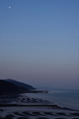 春の夜明けと月と干潟。