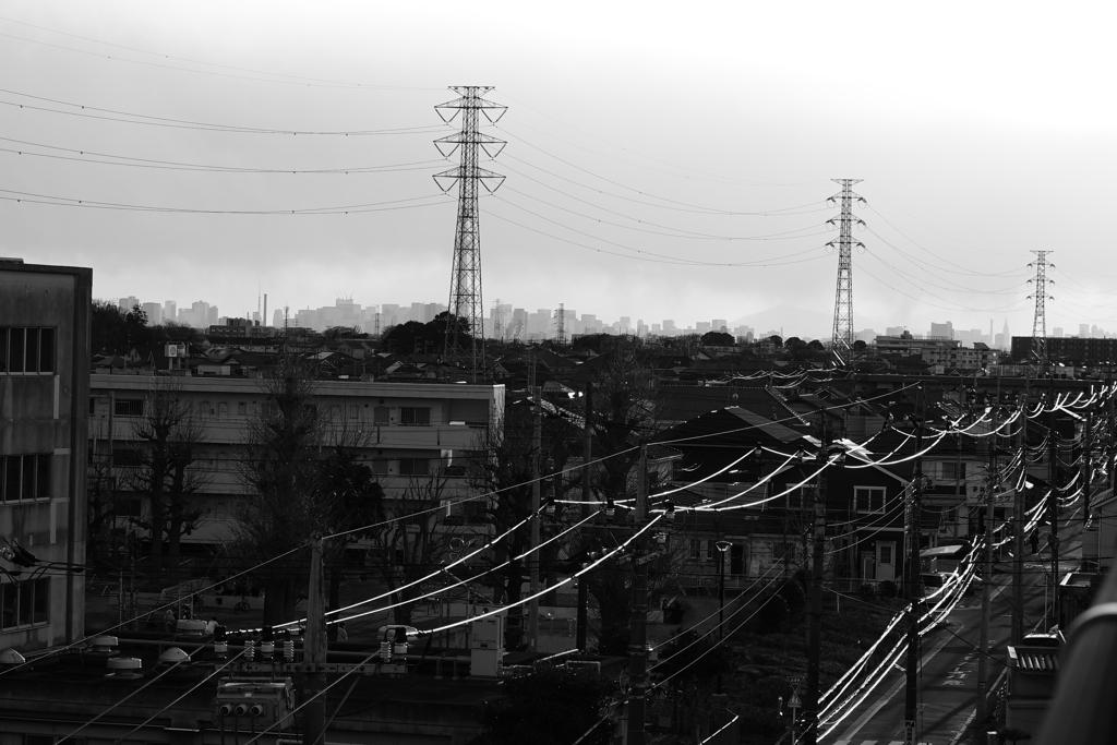 都心遠景と夕陽に光る電線
