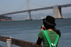 a girl taking a picture of SF bay