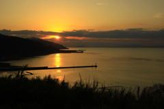 小さな漁港に落ちる夕日