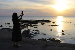 日本海夕日の丘公園から④ 夕日を撮影する女性