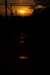 夕日に続くマンホール