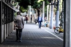 上海を歩く猫背の男