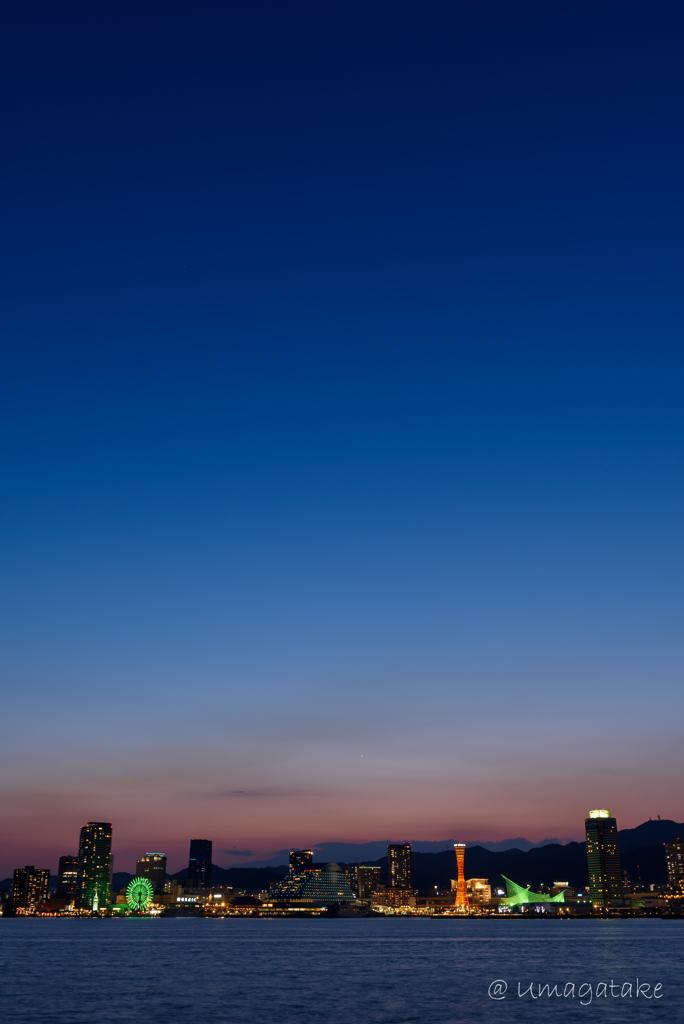 都市の後ろで輝く