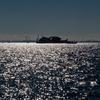 海に反射する太陽光と海に浮かぶ怪しい工場