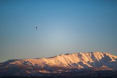 夕日に染まる月山とフライングヒューマノイド(パラグライダー)