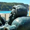 ビーチで寝そべる銅像