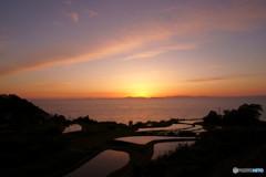 島影に沈みゆく夕日