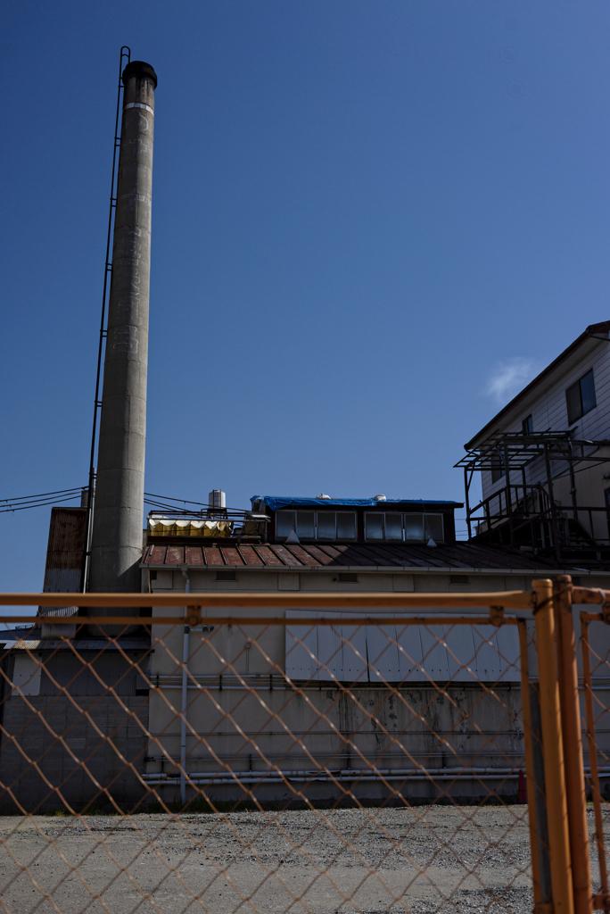銭湯煙突と防護柵の関係性