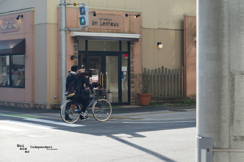 Couple on bike and one man walk