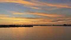 たなびく絹綿と港の夕景