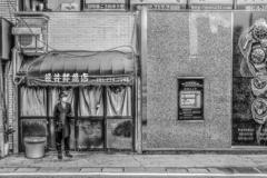 笹井鮮魚店前で煙草を吸う男