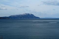 残雪の半島と漁船