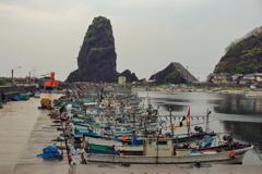 特徴的な岩のある漁港にて