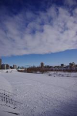 雪の河原に雲と青空