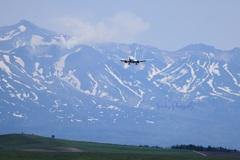 残雪の十勝岳と飛行機
