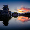 映る朝焼け雲と城