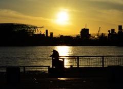 希望の夕日を背に