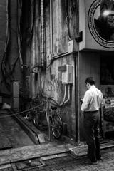 壁、自転車と男
