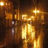 雨で濡れた路面を照らす街灯