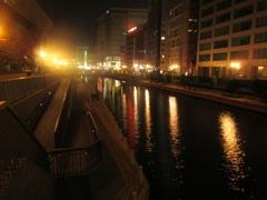 夜の繁華街を流れる川と外灯の光