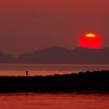 中島に落ちる夕日と釣り人