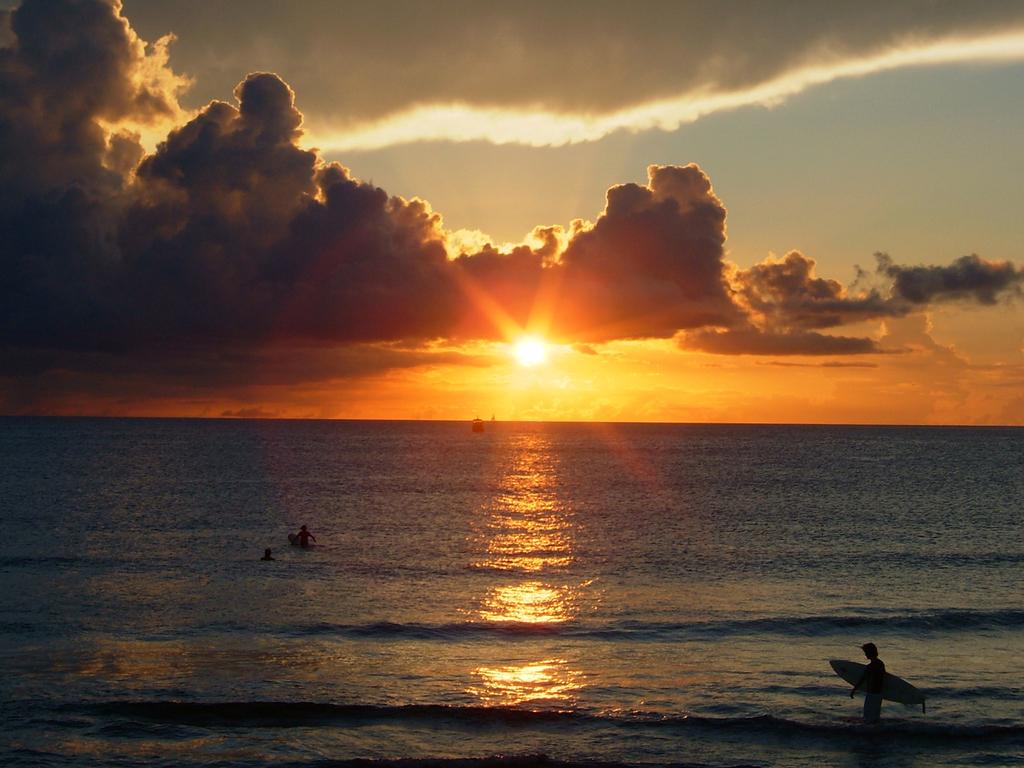 海と夕日とサーファー