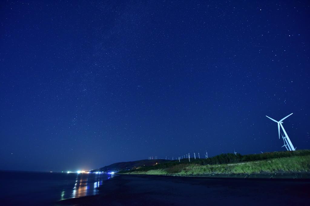 星空と風力発電と波打ち際と