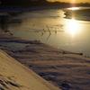 川面に映える夕陽と残雪